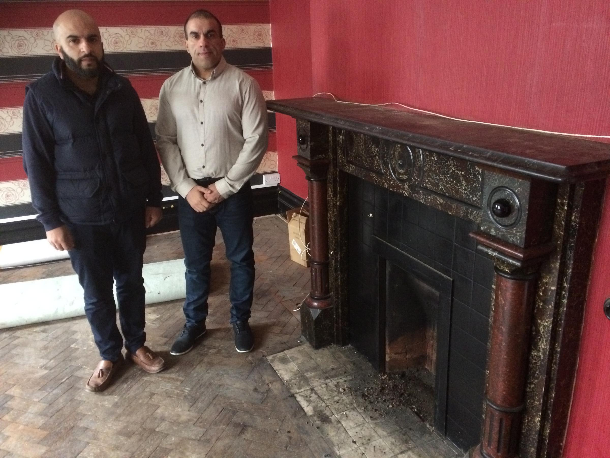 From left, Taliq and Mudassar Hussain next to one of the fireplaces in the old Star Pub building