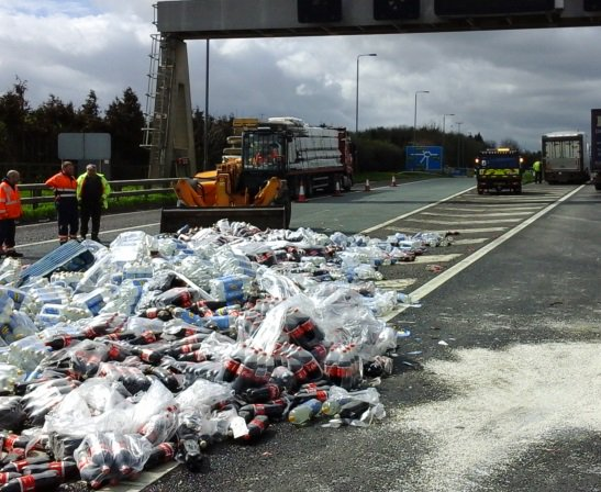 A bulldozer moves in to remove Coca-Cola bottles from the M62. Picture: Highways England