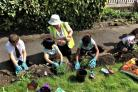 Children from Greengates Primary School help plant flowers at the war memorial