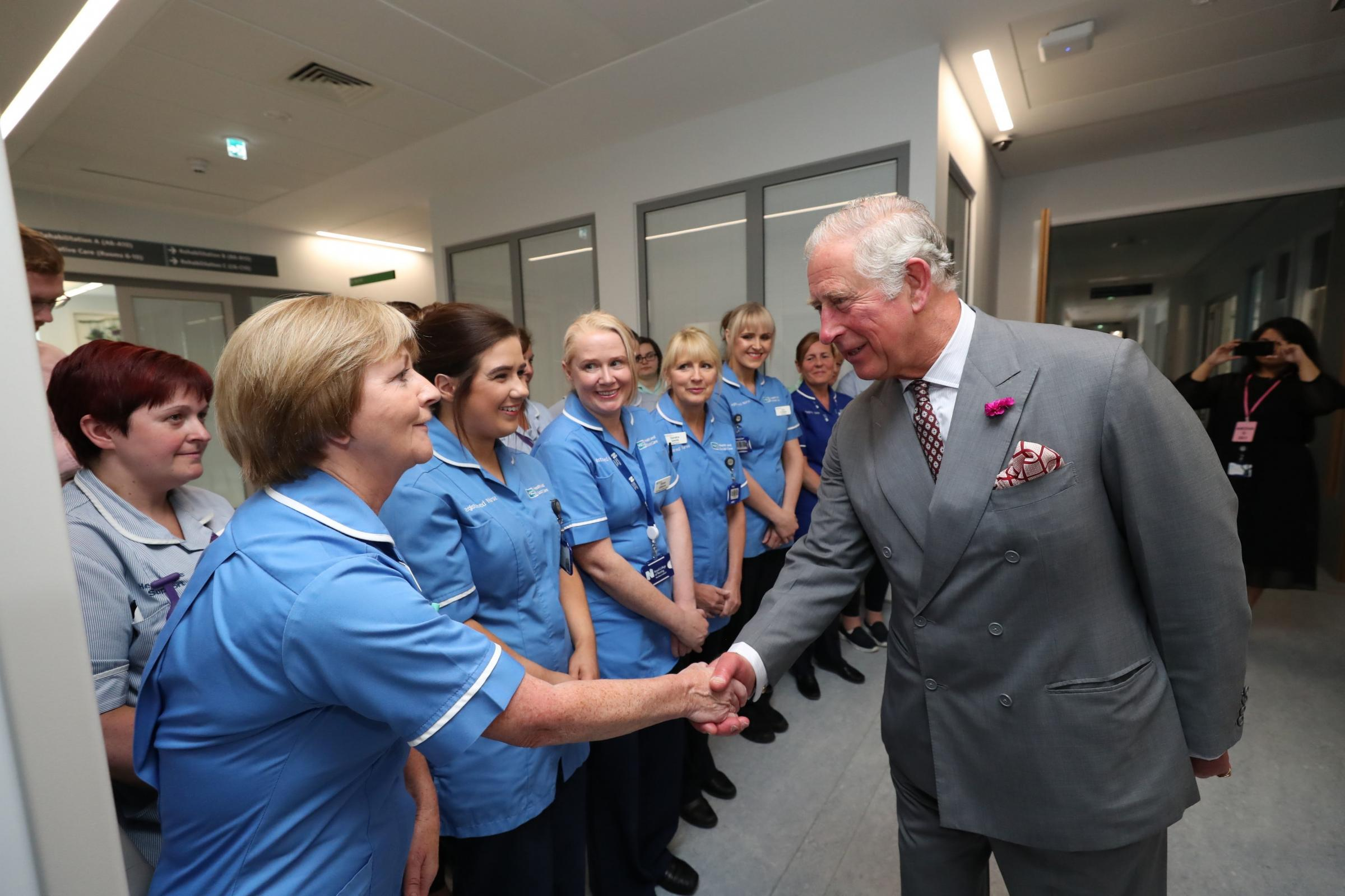 The Prince of Wales greets nurses in the palliative care unit at Omagh Hospital (Niall Carson/PA)