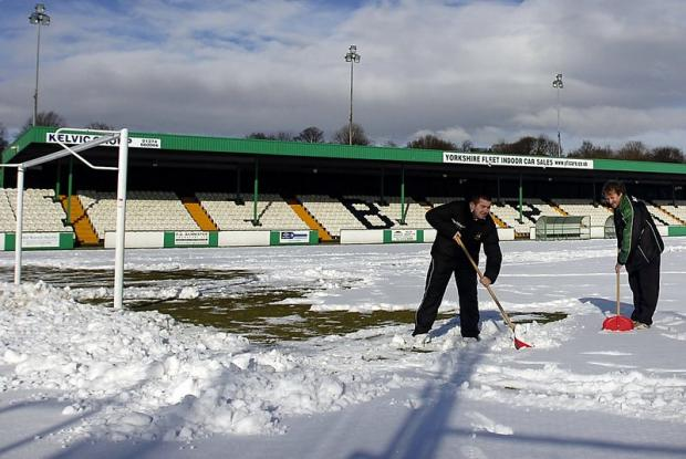 Avenue staff Neil Cairns and Mick Couzens try to clear the Horsfall pitch