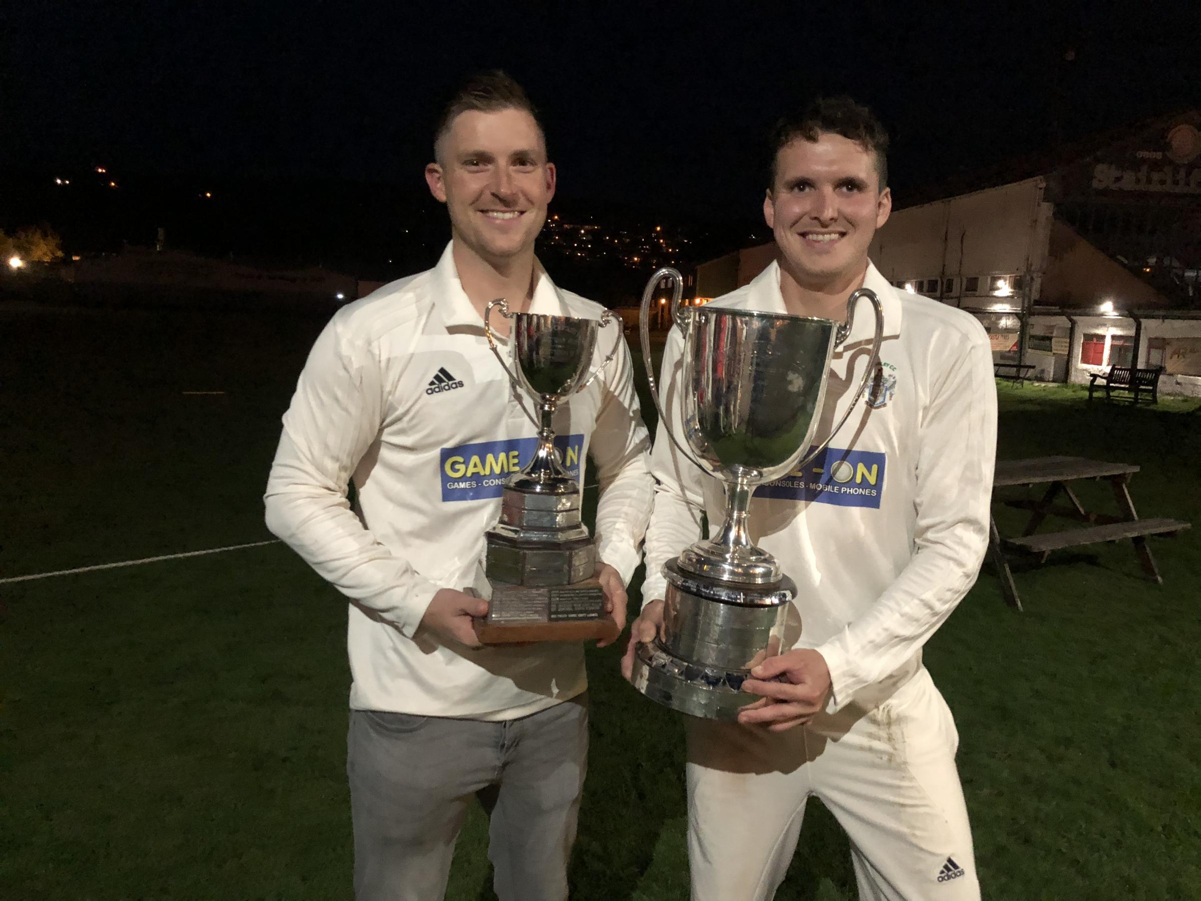 Paul Quinlan (right) proudly holds aloft the Bradford Premier League Championship Two trophy alongside second team captain Alex Towler, whose side won their division too