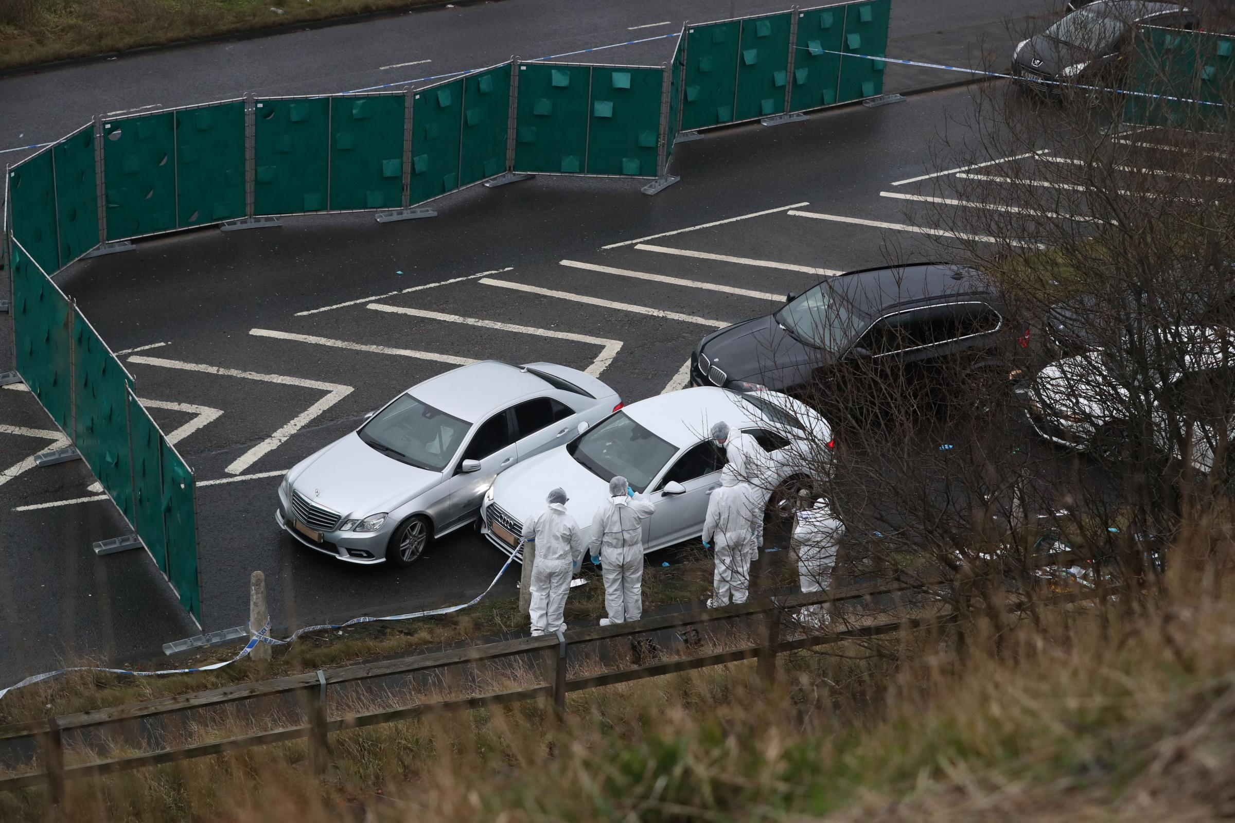 Police forensics officers examine a silver Audi with bullet holes in its windscreen at the scene near junction J24 of the M62 in Huddersfield