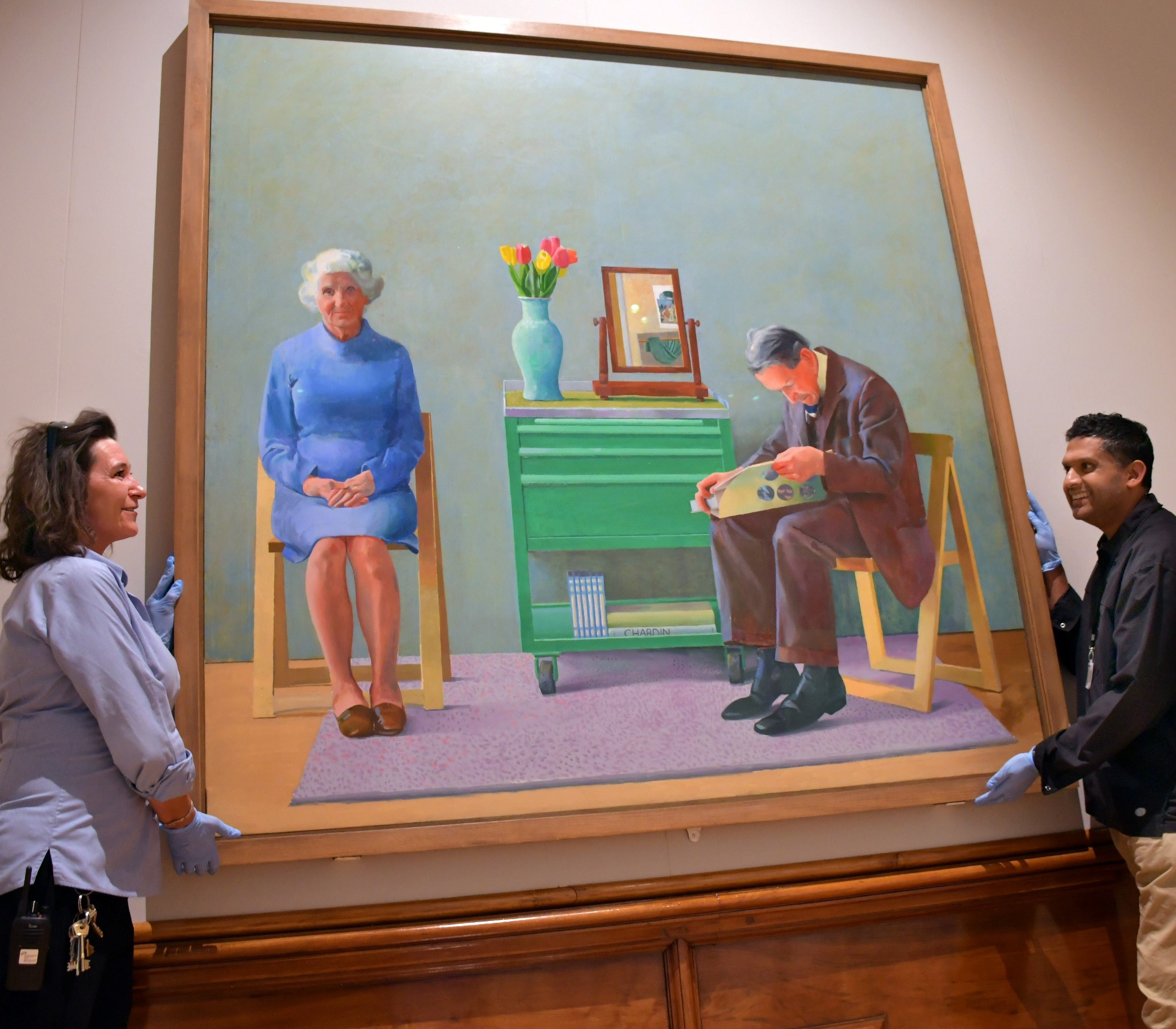Hockney picture  loaned to the Cartwright Hall  by the Tate Gallery. Rowena Broadbent and Nilesh Mistry hang the picture.