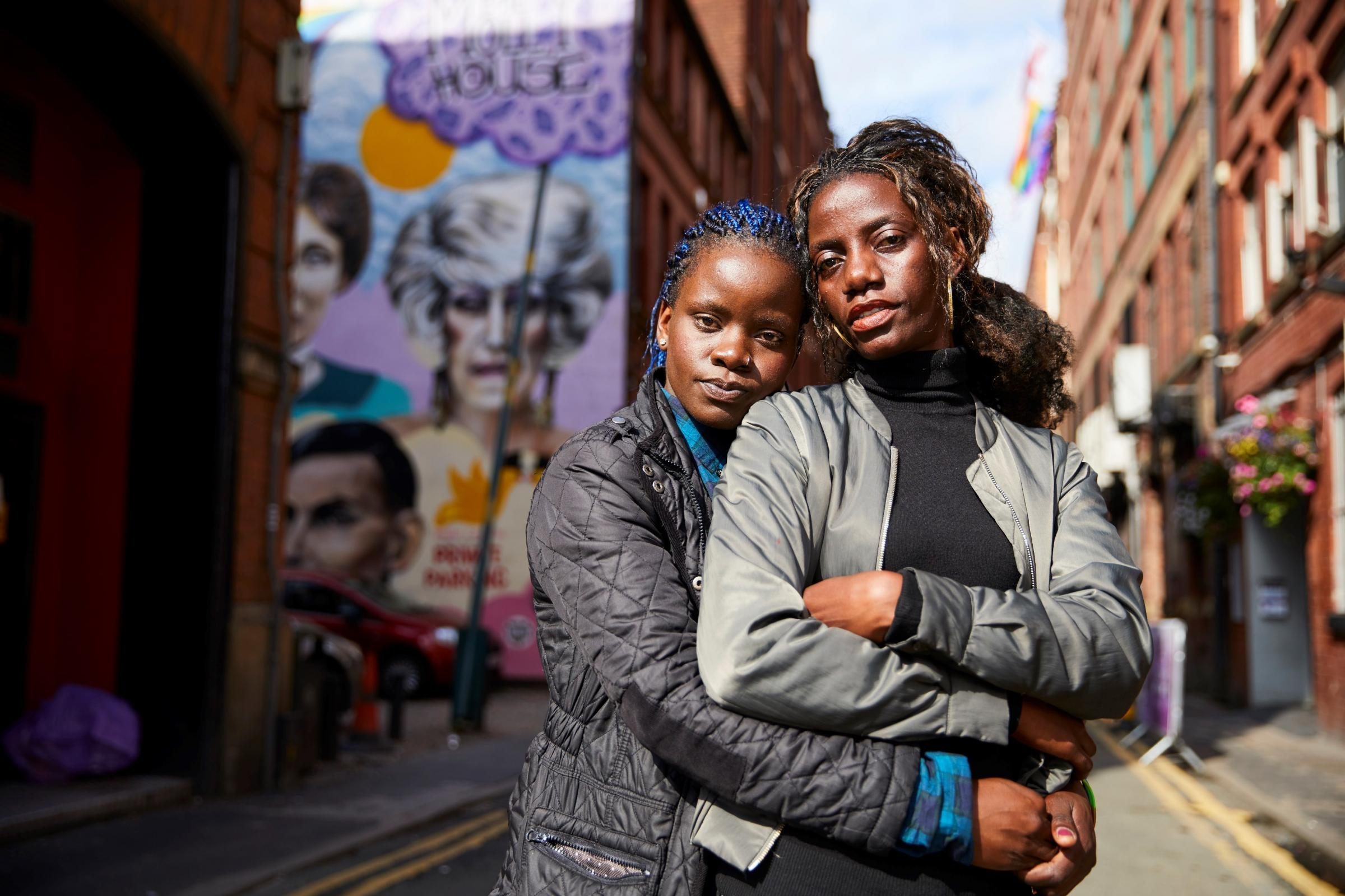 Megan Nankabirwa (blue hair tips) and her partner Lydia Nabukenya in Manchester's gay village. The pair fled Uganda, where homosexuality is outlawed, after they were discovered to be in a relationship. Picture: Christopher Thomond
