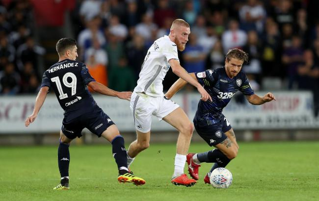 Swansea City's Oli McBurnie gets away from Leeds Pablo Hernandez and Gaetano Berardi during the Sky Bet Championship match at the Liberty Stadium, Swansea..