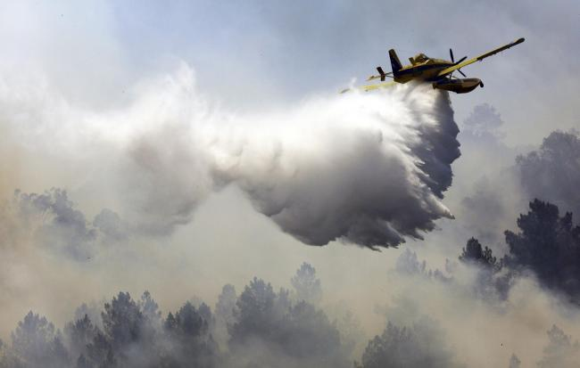 A firefighting airplane drops its load of water on a forest fire raging on a hill across the Tagus river from Vila Velha de Rodao, central Portugal, Thursday, July 27 2017. Almost 2,000 firefighters were deployed at six major forest fires in Portugal Thur