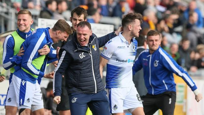 Bristol Rovers manager Graham Coughlan and the dug-out celebrate their stoppage-time winner against City. Pic: Thomas Gadd