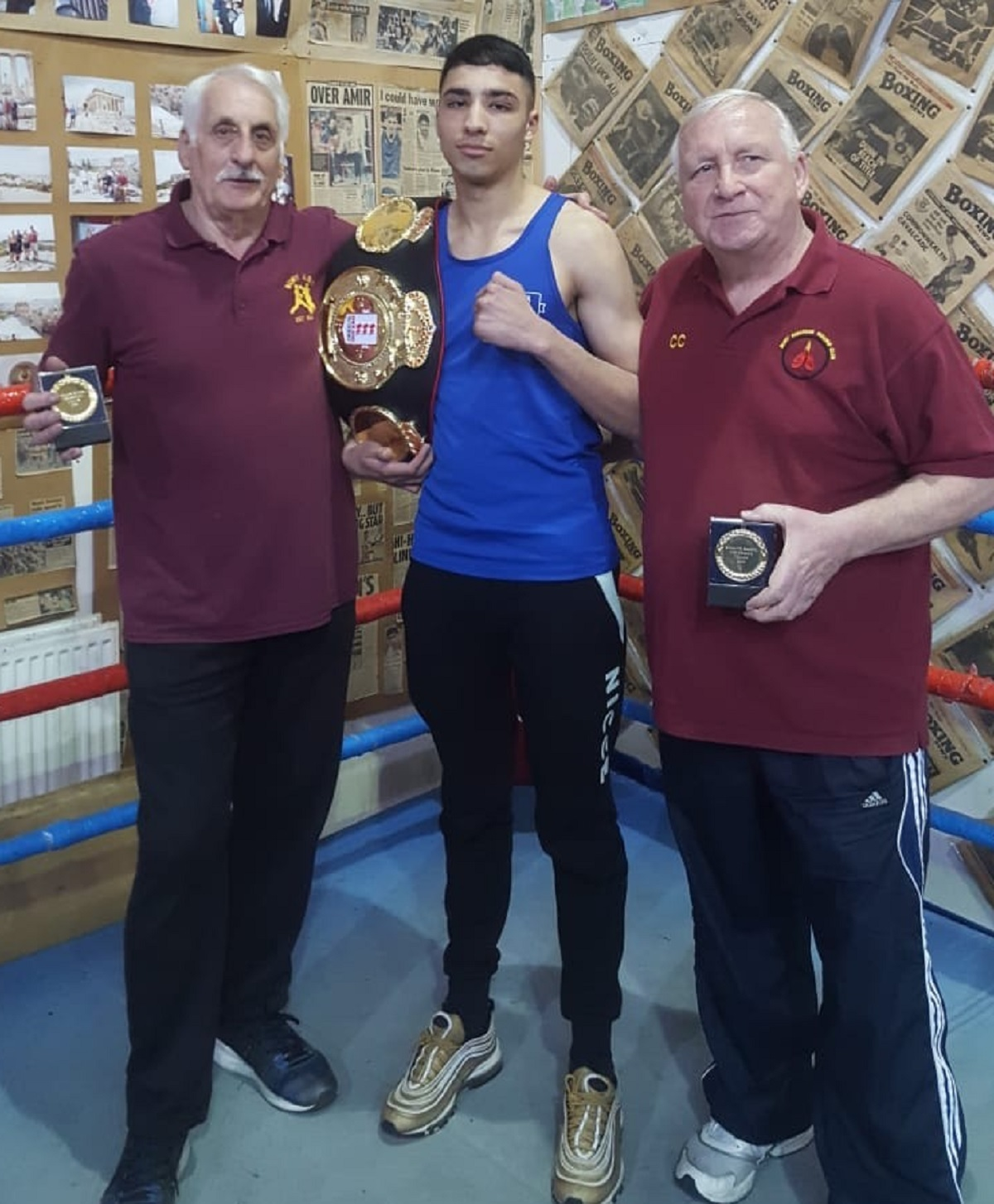 Keighley boxer Muhammed Ibrahim Nadim, with trainers at Bury ABC, Mick Jelley, left, and Colin Carr, poses with his 52-56kg category title belt won at the England Boxing National Amateur Championships 2019 Finals Day