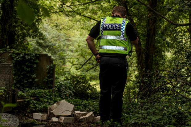 Bradford Telegraph and Argus: A police officer looks at the damage after War Graves vandalised in Hirst Wood Shipley
