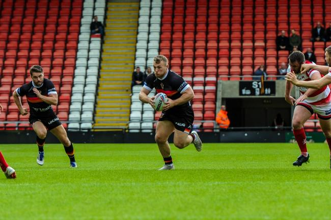 Sam Hallas, centre, goes on a run in Bulls' defeat at Leigh Centurions. Picture: Tom Pearson